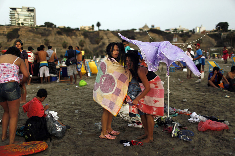 Photo - In this Jan. 13, 2013 photo, girls dress under a damaged umbrella on Agua Dulce beach in Lima, Peru. While Lima's elite spends its summer weekends in gate beach enclaves south of the Peruvian capital, the working class jams by the thousands on a single municipal beach of grayish-brown sands and gentle waves. The only barrier to entry to Agua Dulce beach is two dollars, the price of bus fare to get there and home. (AP Photo/Rodrigo Abd)