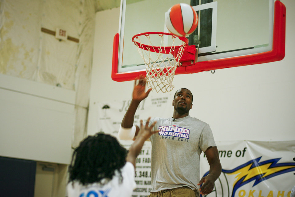 Serge Ibaka goes to block the shot of a child at the Thunder Youth Basketball Camp at the Santa Fe Family Life Center on Tuesday, June 14, 2011. Photo by Zach Gray, The Oklahoman