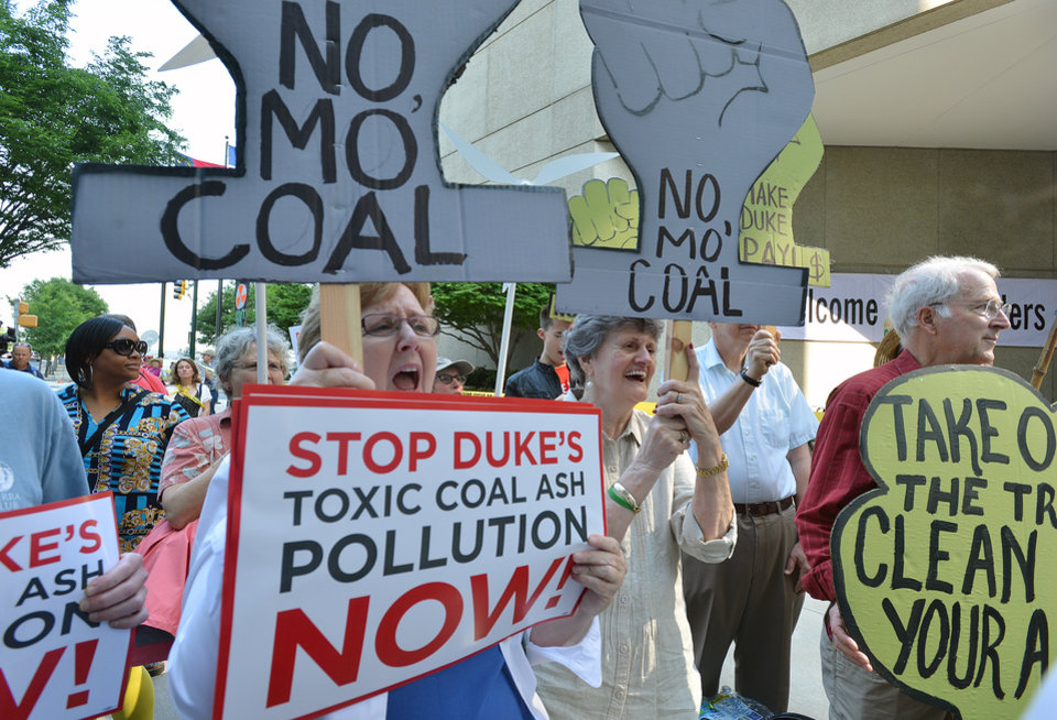 Photo - Protesters carry signs and demonstrate in front of the Duke Energy office building in Charlotte, N.C., Thursday, May 1, 2014, as  shareholders hold their annual meeting. Some Duke Energy investors plan to push the utility's board of directors to investigate issues surrounding a massive coal ash spill that dumped toxic sludge into a 70-mile stretch of a North Carolina river. (AP Photo/The Charlotte Observer, T. Ortega Gaines) MAGS OUT; TV OUT; NEWSPAPER INTERNET ONLY (REV-SHARE)