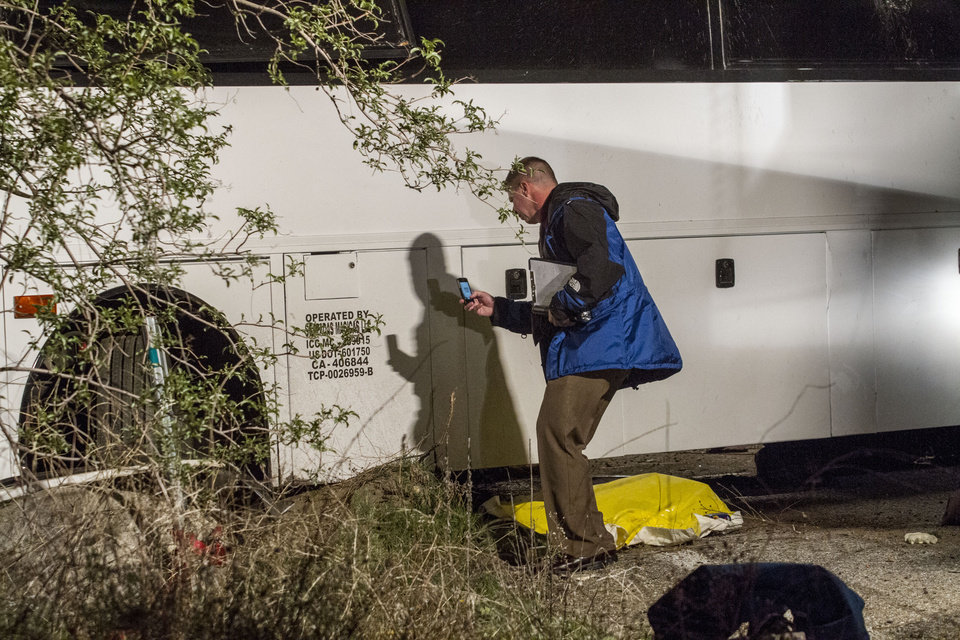 An investigator photographs the scene of the accident where at least eight people were killed and 38 people were injured after a tour bus carrying a group from Tijuana, Mexico crashed with two other vehicles near Yucaipa, Calif., Sunday, Feb. 3, 2013. (AP Photo/Ringo H.W. Chiu)