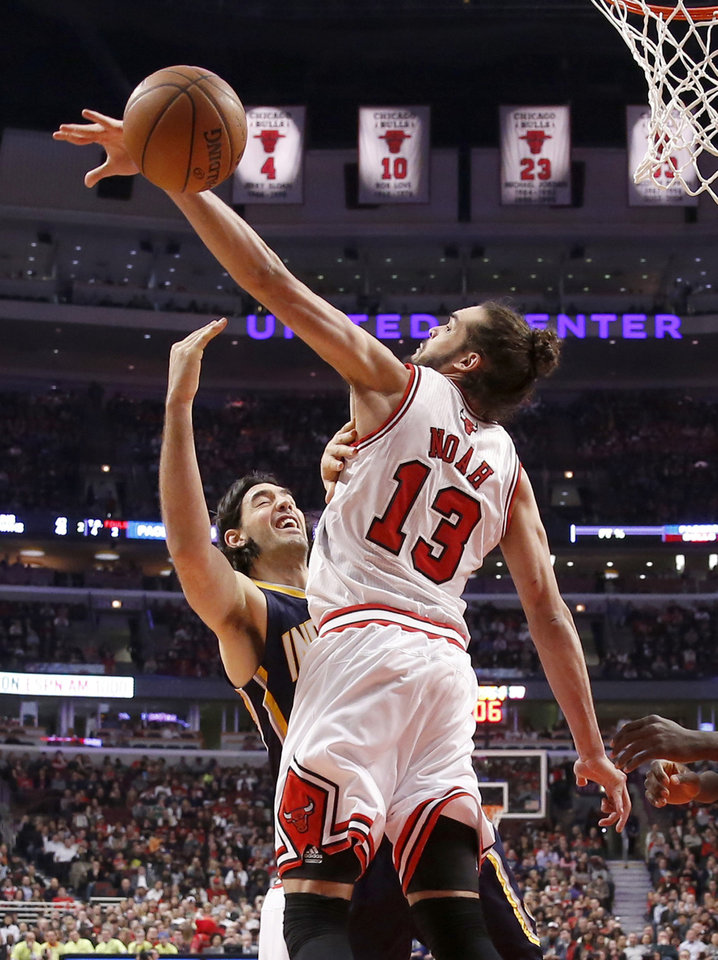 Photo - FILE - In this March 24, 2014 file photo, Chicago Bulls center Joakim Noah (13) blocks the shot of Indiana Pacers forward Luis Scola during the first half of an NBA basketball game in Chicago. A person familiar with the situation says Bulls center Joakim Noah is the NBA's Defensive Player of the Year. The person spoke Monday, April 21, 2014, on the condition of anonymity because the award had not been announced. (AP Photo/Charles Rex Arbogast, File)