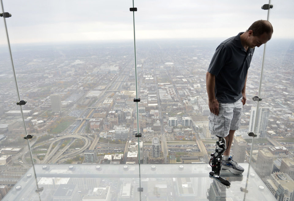 "In this Oct. 25, 2012 photo, Zac Vawter, fitted with an experimental ""bionic"" leg, looks down from the Ledge at the Willis Tower in Chicago. Vawter is training for the world's tallest stair-climbing event where he'll attempt to climb 103 flights to the top of the Willis Tower using the new prosthesis. (AP Photo/Brian Kersey)"