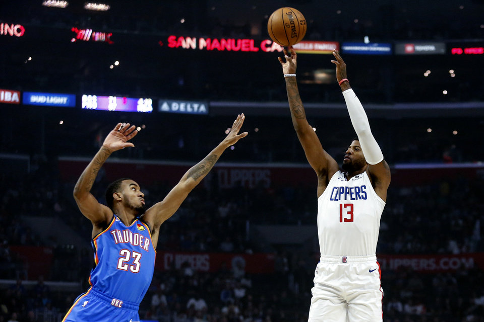 Photo - Los Angeles Clippers' Paul George (13) shoots against Oklahoma City Thunder's Terrance Ferguson (23) during the first half of an NBA basketball game, Monday, Nov. 18, 2019, in Los Angeles. (AP Photo/Ringo H.W. Chiu)