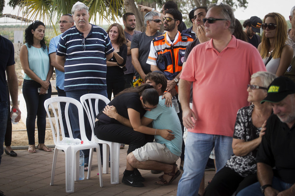 Photo - Parents, center, of four-year-old Israeli boy Daniel Tragerman hug each other during his funeral in a cemetery located next to the Israeli community of Yevul, near the Israeli Gaza border, Sunday, Aug. 24, 2014. Tragerman was killed when a mortar shell hit two cars in the parking lot of Nahal Oz, a small farming community near Gaza. (AP Photo/Oren Ziv)
