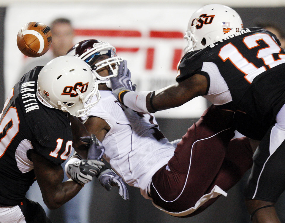 Photo - OSU's Markelle Martin (10) and Johnny Thomas (12) breaks up a pass in the end zone intended for Uzoma Nwachukwu (7) of Texas A&M in the first quarter during the college football game between Texas A&M University and Oklahoma State University (OSU) at Boone Pickens Stadium in Stillwater, Okla., Thursday, Sept. 30, 2010. Photo by Nate Billings, The Oklahoman