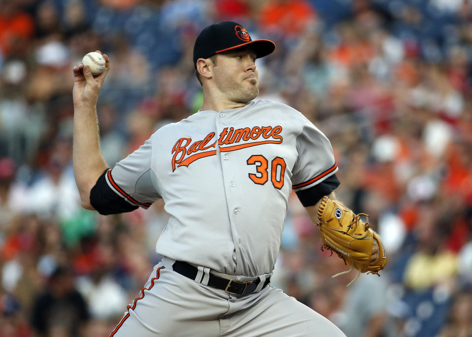 Photo - Baltimore Orioles starting pitcher Chris Tillman (30) throws during the third inning of an interleague baseball game against the Washington Nationals at Nationals Park, Monday, July 7, 2014, in Washington. (AP Photo/Alex Brandon)