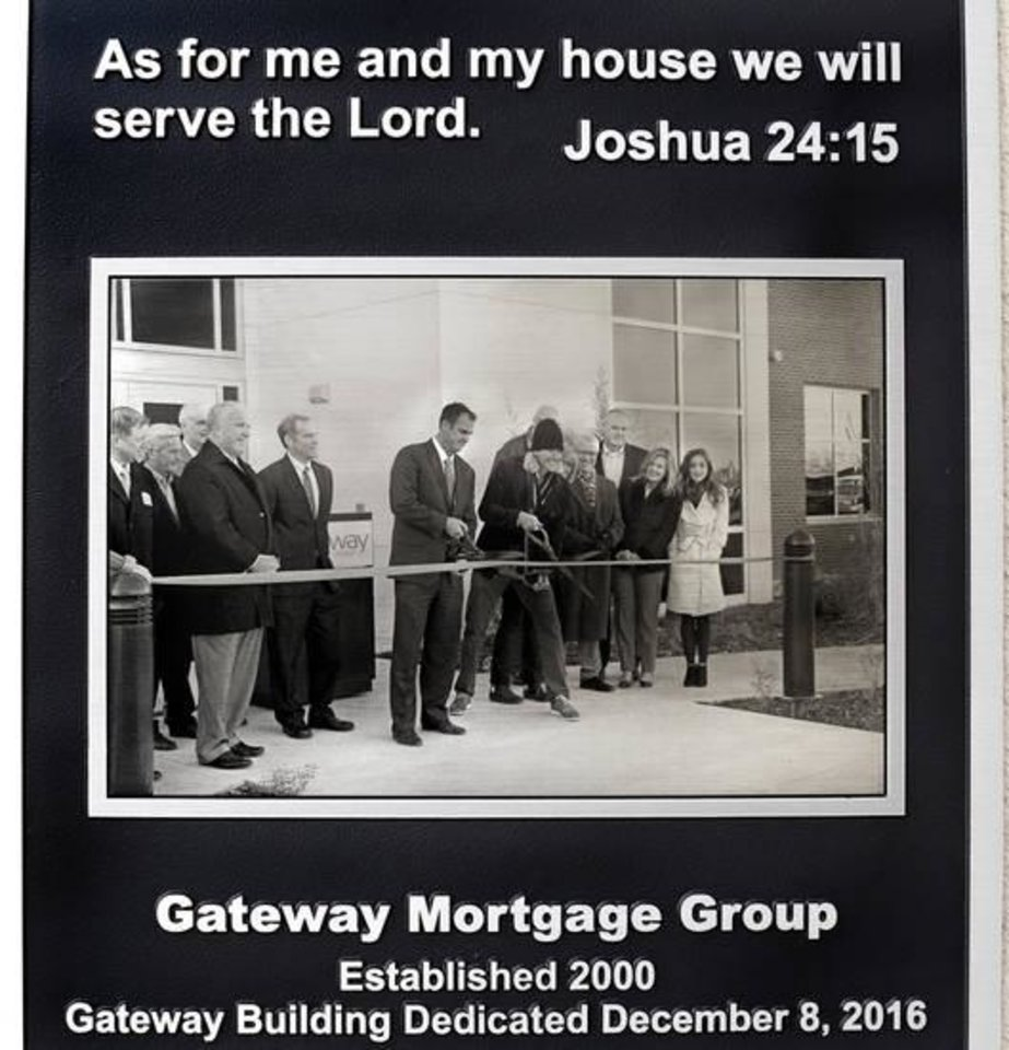 Photo -  This plaque is displayed on an exterior wall near the main entrance to the company headquarters of Gateway First in Jenks. The photo shows Gov. Kevin Stitt and Hobie Higgins holding oversized scissors to cut the ribbon at dedication ceremony in 2016. Stitt is the founder and former CEO of Gateway. [Jim Beckel for The Oklahoman]