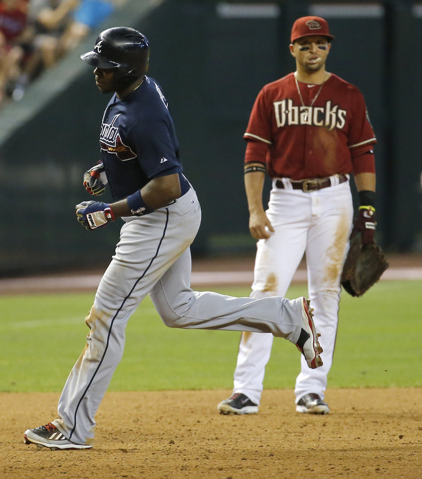 Photo - Atlanta Braves' Justin Upton, left, rounds the bases after hitting a two run home run as Arizona Diamondbacks' Martin Prado looks on during the sixth inning of a baseball game, Sunday, June 8, 2014, in Phoenix. (AP Photo/Matt York)