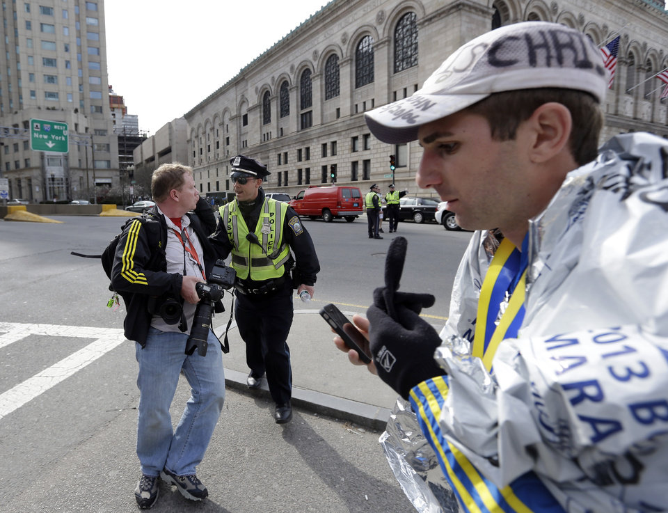 Boston police ask people to leave the area in Copley Plaza in the aftermath of two blasts which exploded near the finish line of the Boston Marathon in Boston Monday, April 15, 2013. (AP Photo/Elise Amendola)  ORG XMIT: MAEA122