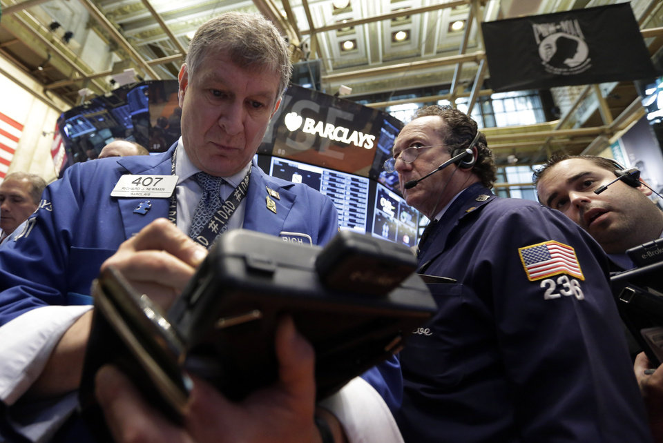 Traders Richard Newman, left, Steven Kaplan, center, and Louis Silk work on the floor of the New York Stock Exchange Thursday, May 2, 2013. Stocks are opening higher on Wall Street, a day after the market\'s biggest fall in two weeks, after General Motors and other big companies announced higher profits. (AP Photo/Richard Drew)