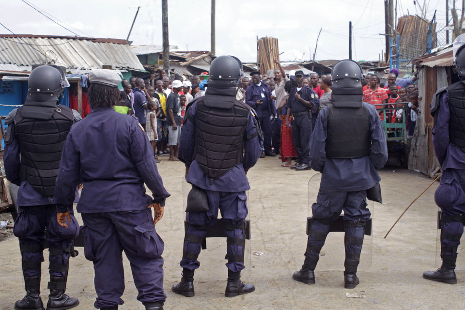 Photo - Liberian security forces with riot gear stop people from leaving the West Point area, that has been hardest hit by the Ebola virus spreading in Monrovia, Liberia, Monday, Aug. 25, 2014. A Liberian doctor who was among three Africans to receive an experimental Ebola drug has died, the country's information minister said Monday.(AP Photo/Abbas Dulleh)
