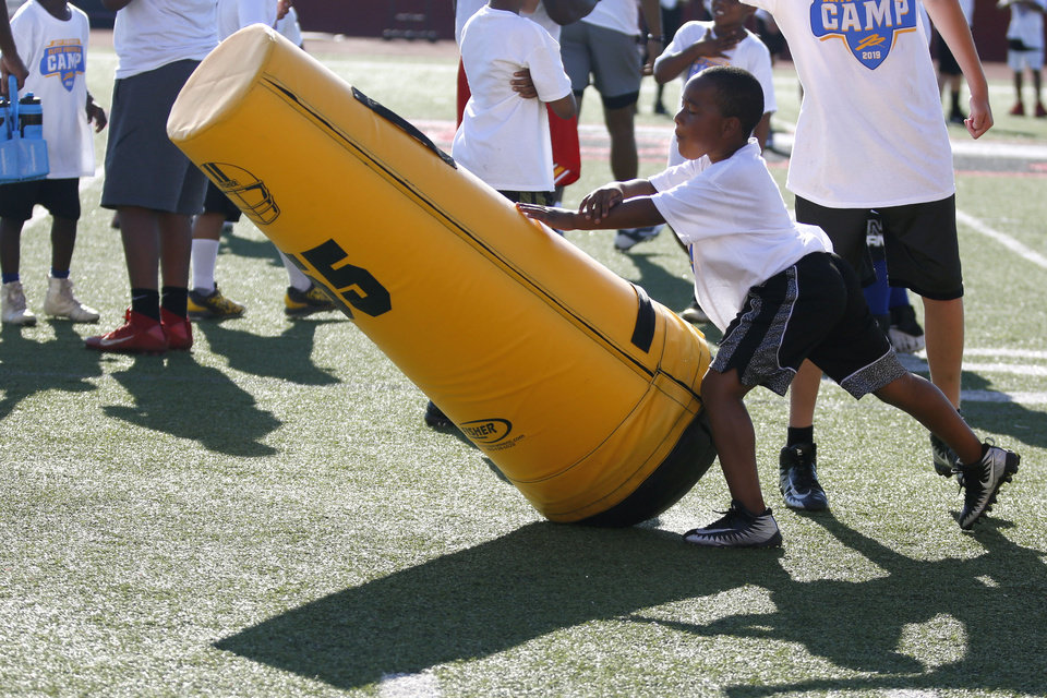 Photo - A child pushes a pop-up dummy at Los Angeles Chargers player Jeff Richards Elite Football Camp at Del City High School in Del City, Oklahoma on July 13, 2019. [Paxson Haws/The Oklahoman]