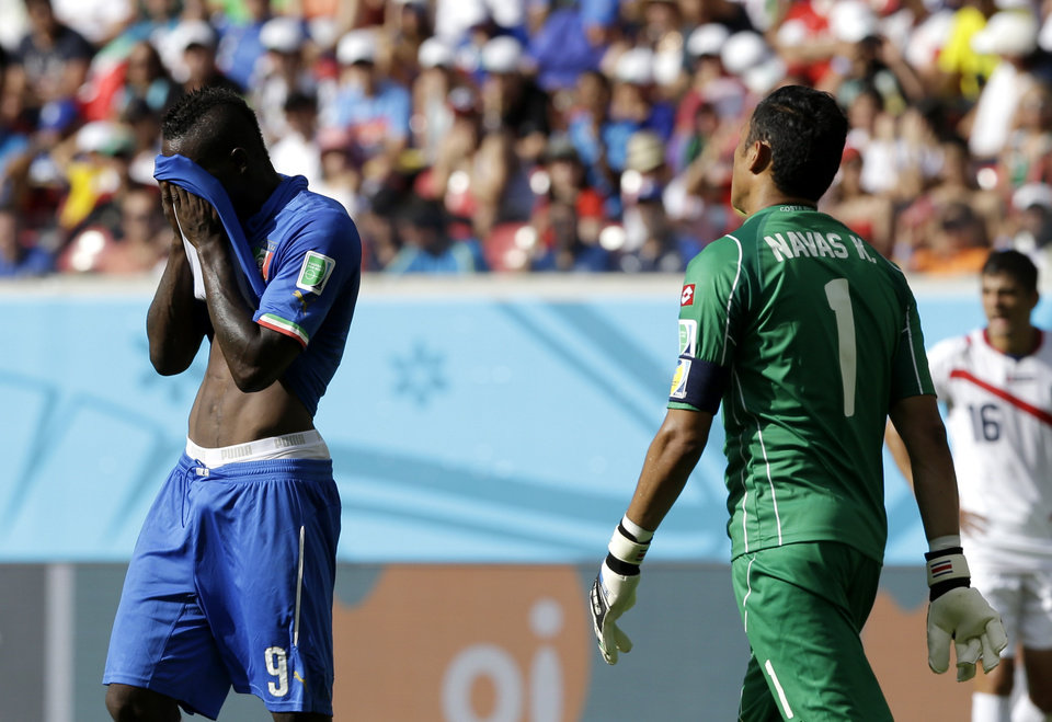 Photo - Italy's Mario Balotelli, left, wipes his face in front of Costa Rica's goalkeeper Keylor Navas during the group D World Cup soccer match between Italy and Costa Rica at the Arena Pernambuco in Recife, Brazil, Friday, June 20, 2014.  (AP Photo/Ricardo Mazalan)