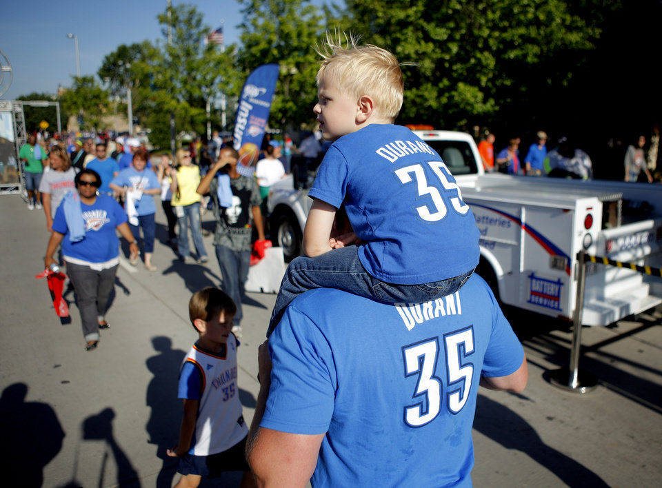 Photo - Bryan Scagnetti of Oklahoma City carries his son, Preston Scagnetti, 3, outside the arena before Game 4 of the Western Conference Finals between the Oklahoma City Thunder and the San Antonio Spurs in the NBA playoffs at the Chesapeake Energy Arena in Oklahoma City, Saturday, May 31, 2012. Photo by Bryan Terry, The Oklahoman