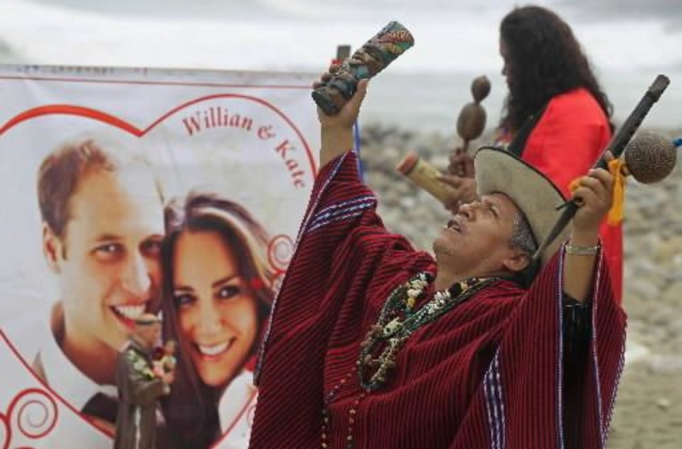Photo - A Peruvian shaman performs in front of a photo of the Britain's Prince William and Kate Middleton during a ritual to send good vibes to their royal wedding on La Herradura beach in Lima, Peru, Wednesday April 27, 2011. Kate and Prince William will marry on Friday. (AP Photo/Martin Mejia)