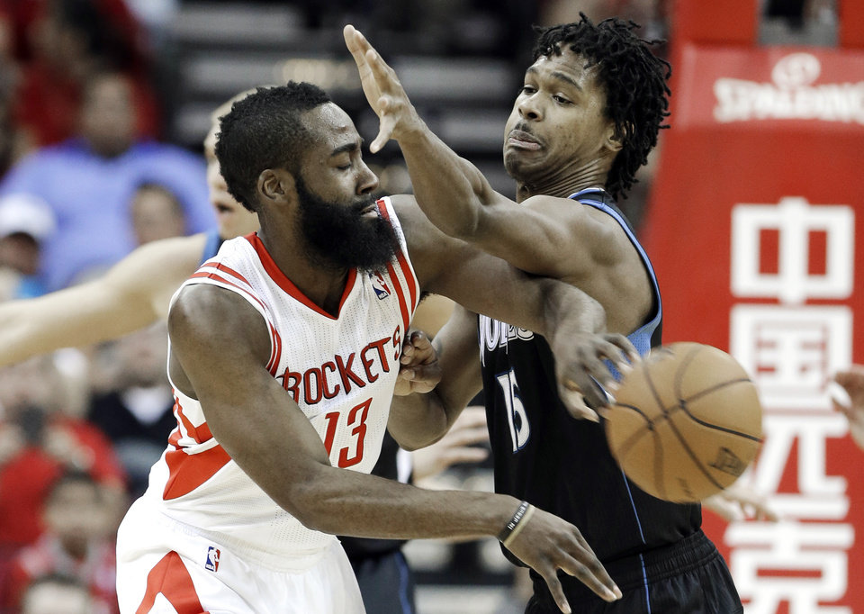 Photo - Houston Rockets' James Harden (13) tries to pass the ball around Minnesota Timberwolves' Mickael Gelabale (15) in the first half of an NBA basketball game Friday, March 15, 2013, in Houston. (AP Photo/Pat Sullivan)