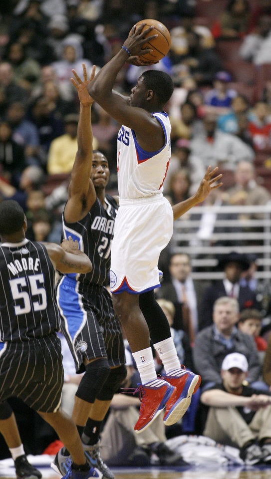 Orlando Magic's E'Twaun Moore (55) and Maurice Harkless (21) defend as Philadelphia 76ers' Jrue Holiday (11) shoot a jump shot in the first half of an NBA basketball game, Tuesday, Feb. 26, 2013, in Philadelphia. (AP Photo/H. Rumph Jr)