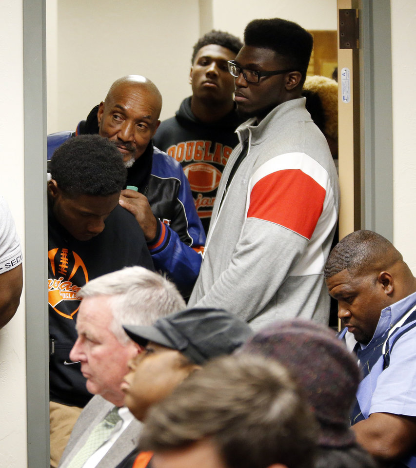 Photo - Douglass players and supporters listen from the hallway during a special meeting of the Oklahoma Secondary School Activities Association board of directors at the OSSAA Office, 7300 N. Broadway Extension in Oklahoma City, Wednesday, Dec. 3, 2014. The board considered an appeal by Douglass to replay the Class 3A quarterfinal football playoff game against Locust Grove from the point of a misapplied rule that negated a late Douglass touchdown or in its entirety. The board denied the appeal. Photo by Nate Billings, The Oklahoman