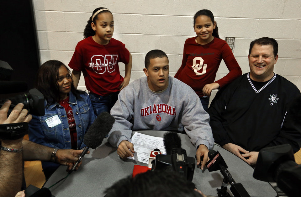 Photo - Jordan Evans, son of University of Oklahoma former defensive lineman Scott Evans (right), signs a letter of intent to play for OU at a signing day assembly at Norman North High School on Wednesday, Feb. 6, 2013, in Norman, Okla.  Mother Tenika and sisters Jacie, 12, and Jessiika, 11, right, are with him.  Photo by Steve Sisney, The Oklahoman