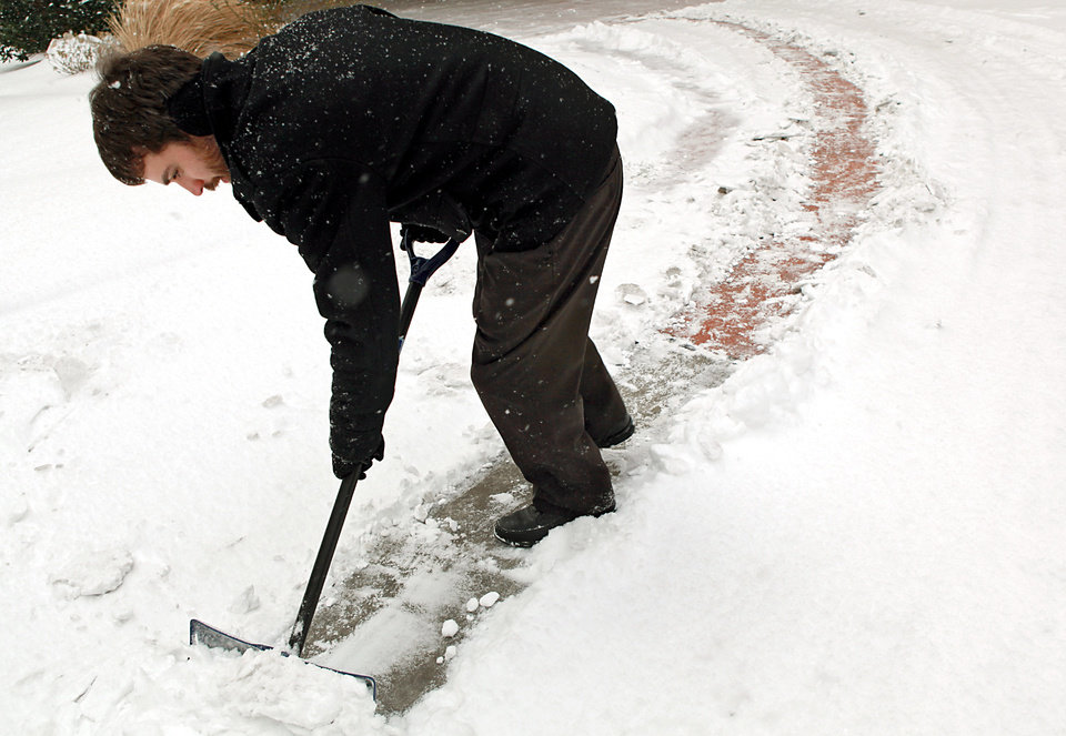 Photo - Chad Ingersoll, a Bellman at the Downtown Oklahoma City Sheraton, shovels the driveway to the hotel during a snow storm in Oklahoma City on Wednesday, Feb. 9, 2011. Photo by John Clanton, The Oklahoman