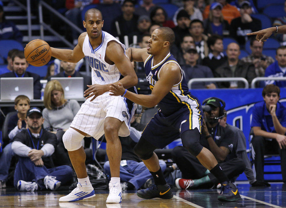 Orlando Magic guard Arron Afflalo (4) controls the ball against Utah Jazz guard Randy Foye (8) during the first half of an NBA basketball game, Sunday, Dec. 23, 2012, in Orlando, Fla. (AP Photo/Scott Iskowitz)