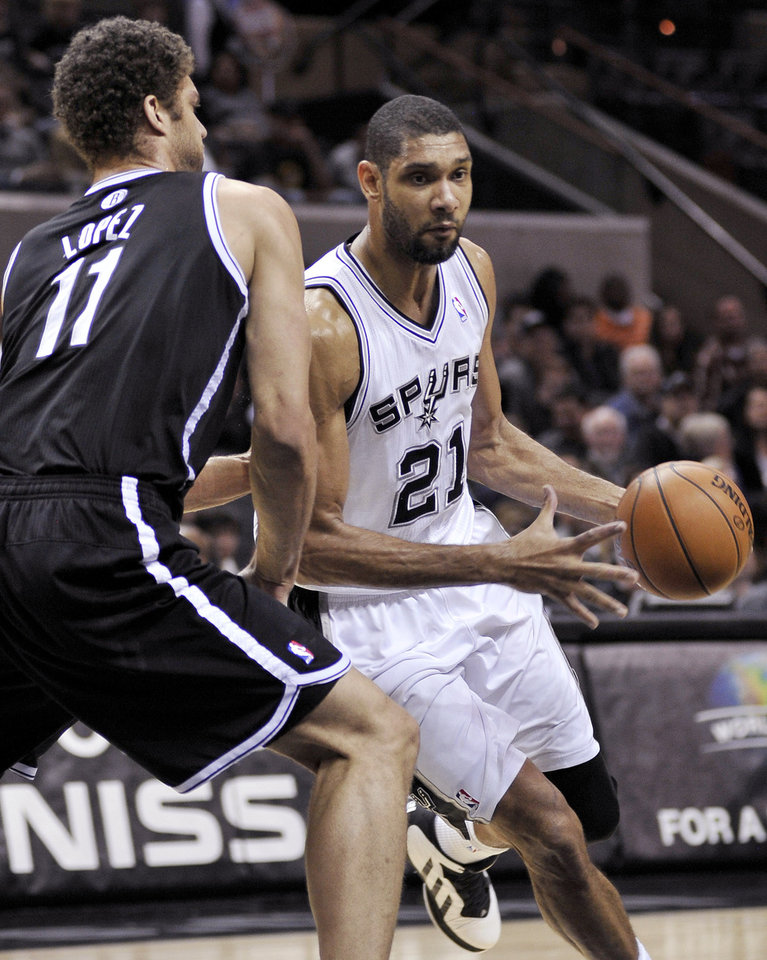 San Antonio Spurs' Tim Duncan (21) drives around Brooklyn Nets' Brook Lopez during the first half of an NBA basketball game, Monday, Dec. 31, 2012, in San Antonio. (AP Photo/Darren Abate)