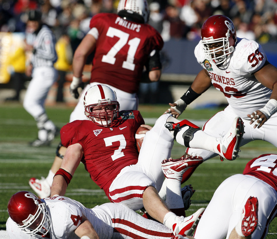 Photo - Toby Gerhart (7) is tackled for a loss by Ryan reynolds (4) during the second half of the Brut Sun Bowl college football game between the University of Oklahoma Sooners (OU) and the Stanford University Cardinal on Thursday, Dec. 31, 2009, in El Paso, Tex.   Photo by Steve Sisney, The Oklahoman