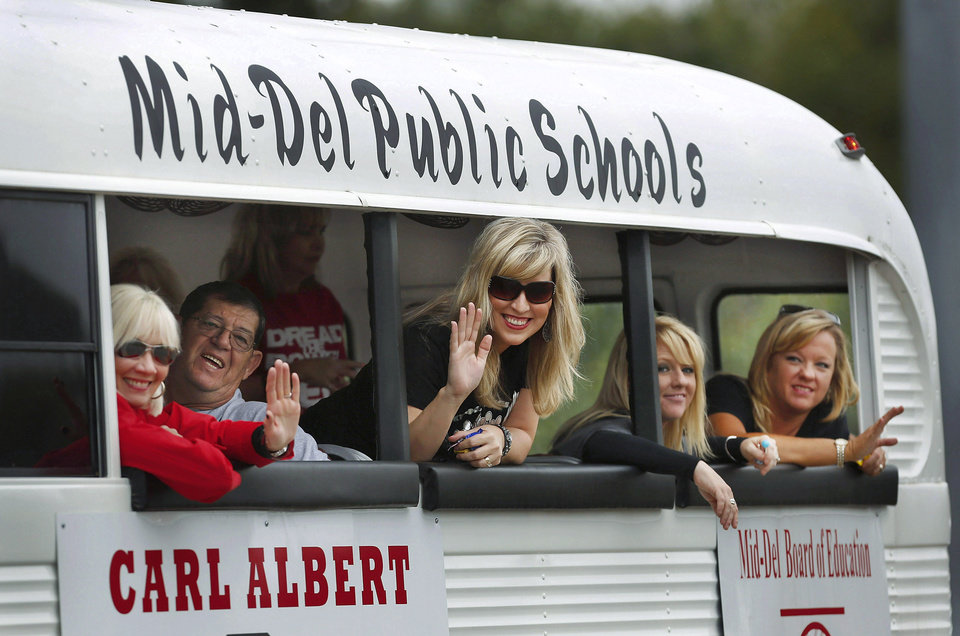 From left, Dr. Pam Deering, superintendent for Mid-Del Schools, Le Roy (cq, there is a space between the two names) Porter, board member, Stacey Boyer, Kandy Perkins and Sydni Boyd, representing the school administration office and the school board,  wave to parade watchers from  inside a white bus. Carl Albert High School is celebrating its 50th birthday this year and students and alumni participated in homecoming week activities, including a two-mile long parade before the football game on Friday, Oct. 12, 2012.    Photo by Jim Beckel, The Oklahoman