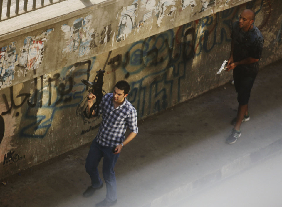 Photo - Two civilians holding guns walk on a street in the Zamalek neighborhood of Cairo, Egypt, Friday, Aug. 16, 2013. Gunfire rang out over a main Cairo overpass and police fired tear gas as clashes broke out after tens of thousands of Muslim Brotherhood supporters took to the streets Friday across Egypt in defiance of a military-imposed state of emergency following the country's bloodshed earlier this week. (AP Photo/Manoocher Deghati) WHITE CASTING AT LOWER RIGHT DUE TO WINDOW GLASS REFLECTION