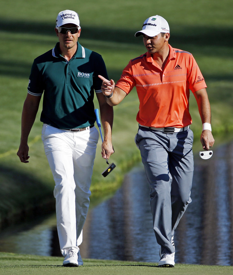 Photo - Jason Day, right, of Australia, speaks with Henrik Stenson, of Sweden, as they walk up the 16th fairway during the first round of the Masters golf tournament Thursday, April 10, 2014, in Augusta, Ga. (AP Photo/Matt Slocum)