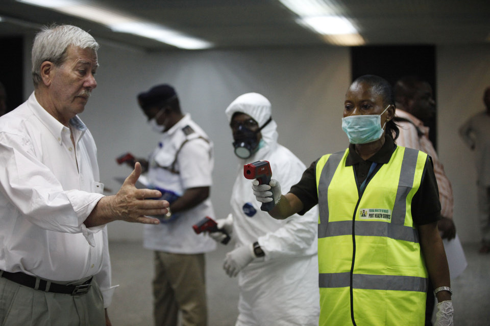 Nigerian port health officials uses a thermometer on a worker at the arrivals hall of Murtala Muhammed International Airport in Lagos, Nigeria, Wednesday, Aug. 6, 2014. A Nigerian nurse who treated a man with Ebola is now dead and five others are sick with one of the world\'s most virulent diseases, authorities said Wednesday as the death toll rose to at least 932 people in four West African countries. (AP Photo/Sunday Alamba)
