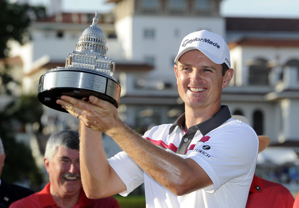 Photo - Justin Rose, of England, poses with the trophy after he won the Quicken Loans National golf tournament, Sunday, June 29, 2014, in Bethesda, Md. (AP Photo/Nick Wass)