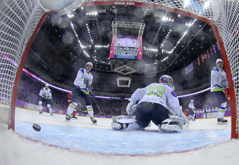 Photo - Slovenia goaltender Robert Kristan looks for the puck as it slides across the goal line shot by Russia's Russia forward Valeri Nichushkin in the third period of a men's ice hockey game at the 2014 Winter Olympics, Thursday, Feb. 13, 2014, in Sochi, Russia. Russia won 5-2 (AP Photo/Bruce Bennett, Pool)