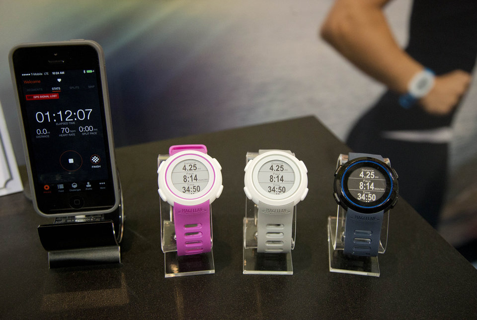 Photo - Magellan Echo smart sports watches sit on display at the International Consumer Electronics Show, Wednesday, Jan. 8, 2014, in Las Vegas. The watch can sync with mobile devices to make the most out of the user's sports apps. (AP Photo/Julie Jacobson)
