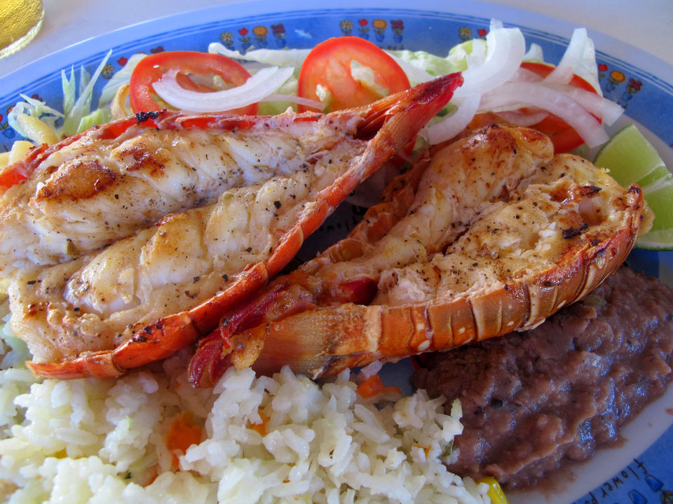 Photo - This November 2012 photo shows fresh grilled lobster at a popular lunch spot known as Velasquez Restaurant after just being caught in the sea off Isla Mujeres, Mexico. Isla Mujeres, or Island of Women, is a tiny 5-mile-long, half-mile wide island just a half-hour's ferry ride across from Cancun, with far fewer visitors and a much calmer, romantic atmosphere. (AP Photo/Amanda Lee Myers)