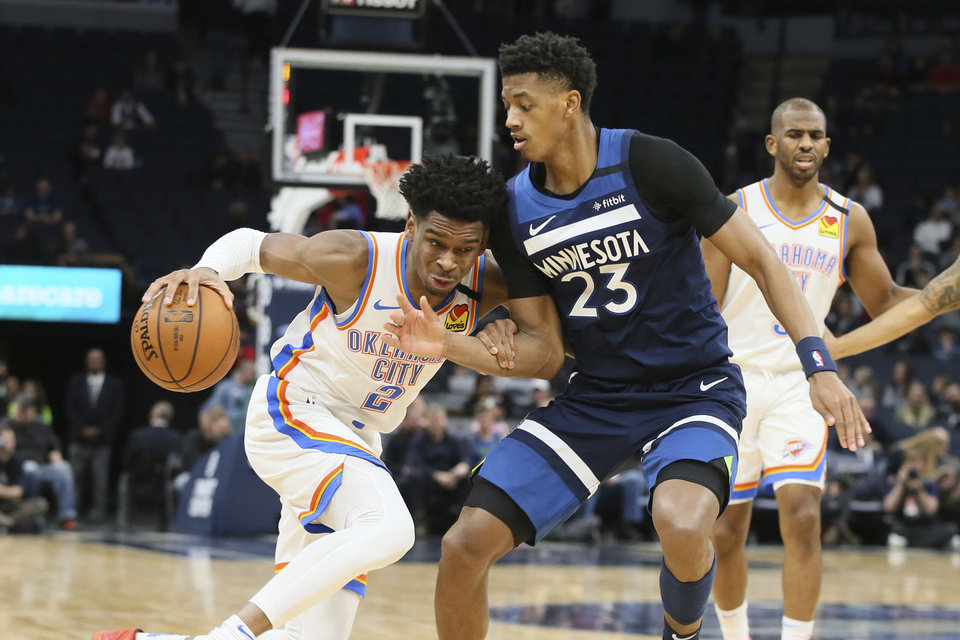 Photo - Oklahoma City Thunder's Shai Gilgeous-Alexander, left, of Canada, drives on Minnesota Timberwolves' Jarrett Culver in the second half of an NBA basketball game Monday, Jan. 13, 2020, in Minneapolis. The Thunder won 117-104. (AP Photo/Jim Mone)
