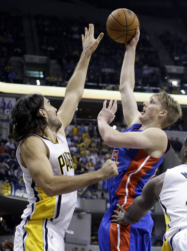 Photo - Detroit Pistons forward Kyle Singler, right, shoots over Indiana Pacers forward Luis Scola in the first half of an NBA basketball game in Indianapolis, Monday, Dec. 16, 2013.  (AP Photo/Michael Conroy)