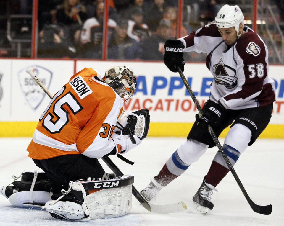 Photo - Philadelphia Flyers' Steve Mason, left, gloves the puck as Colorado Avalanche'  Patrick Bordeleau, right, moves in during the first period of an NHL hockey game, Thursday, Feb. 6, 2014, in Philadelphia. (AP Photo/Tom Mihalek)