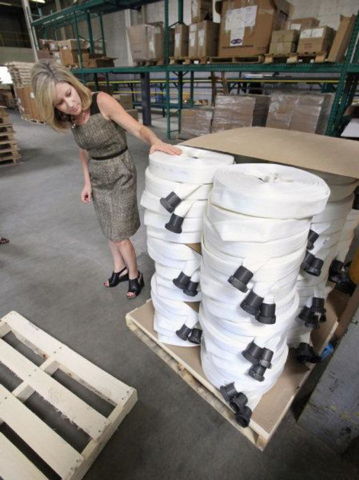 Photo - Lauren White, presidnet and CEO of NewView Oklahoma, looks at fire hoses that were manufactured at NewView (CQ NewView one word) in Oklahoma City.  PAUL B. SOUTHERLAND - PAUL B. SOUTHERLAND