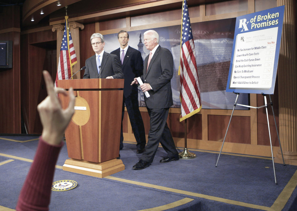 Photo - A reporter raises her hand Monday as, from left, Sen. Tom Coburn, R-Muskogee, Sen. John Thune, R-S.D., and Sen. Saxby Chambliss, R-Ga., take questions on health care. AP Photo