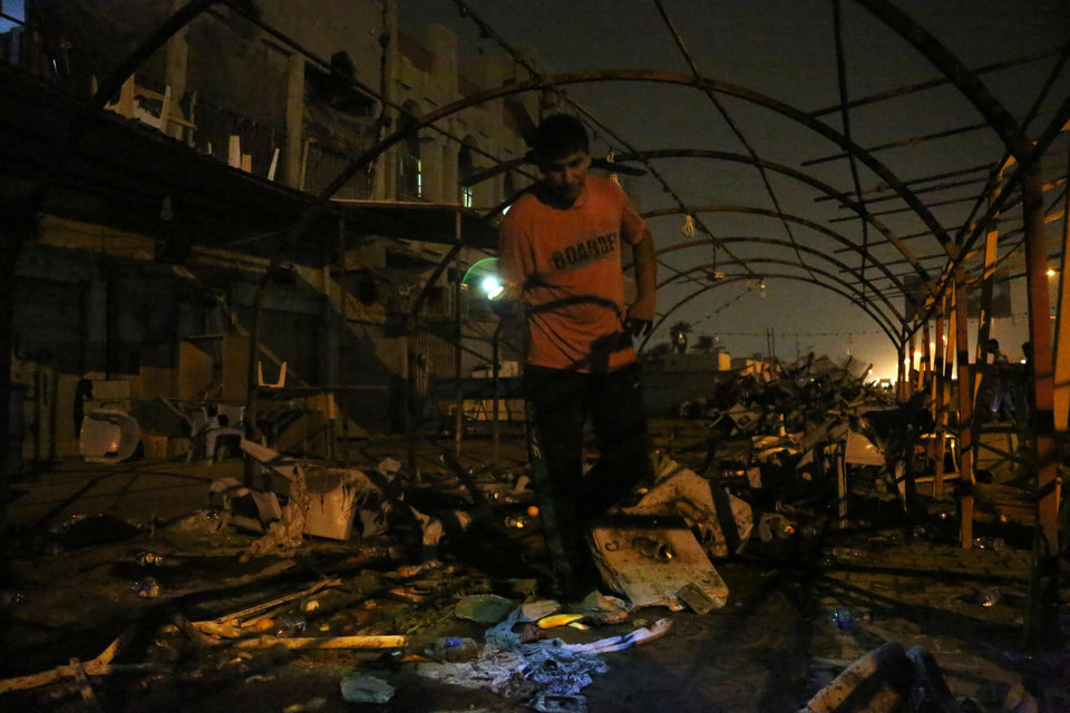 Photo - A man inspects the site of a double suicide bomb attack,  in the Shiite neighborhood of Sadr city in Baghdad, Iraq, Saturday, Sept. 21, 2013. Two suicide bombers, one in an explosives-laden car and the other on foot, hit a cluster of funeral tents packed with mourning families in a Shiite neighborhood in Baghdad, the deadliest in a string of attacks around Iraq that killed at least 92 on Saturday. (AP Photo/Hadi Mizban)