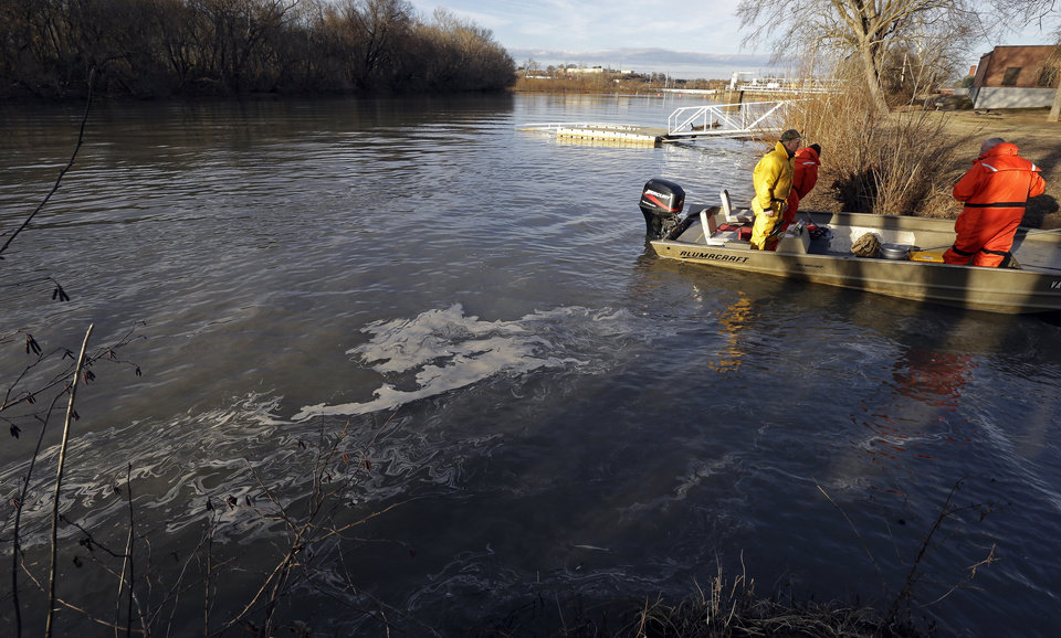 Photo - State and federal officials dock after collecting sediment samples as coal ash surfaces on the water on the Dan River in Danville, Va., Wednesday, Feb. 5, 2014. A coal ash spill from a break in a 48-inch storm water pipe at the Dan River Power Plant in Eden N.C. on Sunday released  up to 82,000 tons of ash according to Duke Energy. (AP Photo/Gerry Broome)