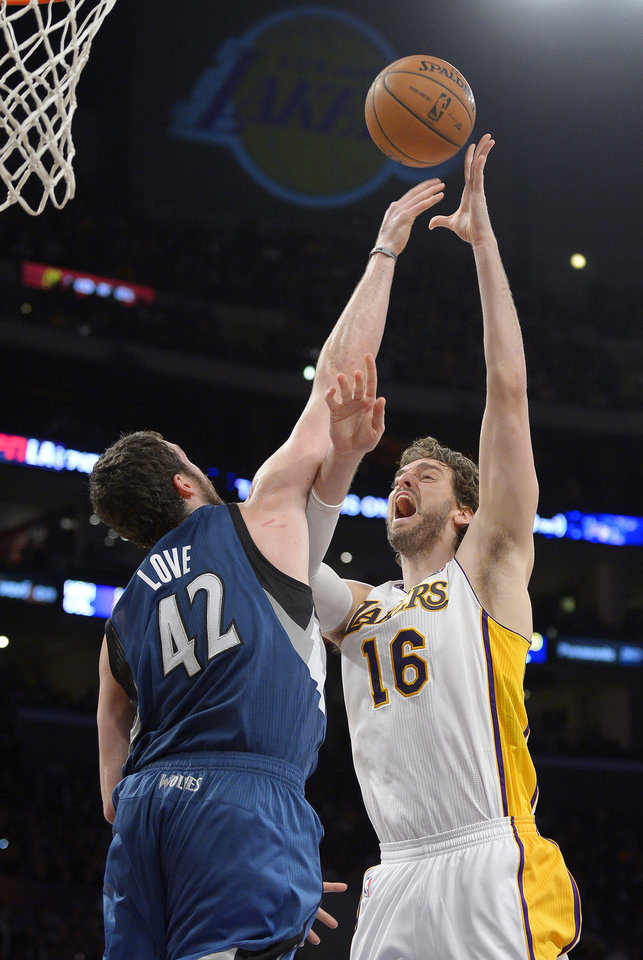 Photo - Los Angeles Lakers center Pau Gasol, right, of Spain, puts up a shot as Minnesota Timberwolves forward Kevin Love defends during the first half of an NBA basketball game, Sunday, Nov. 10, 2013, in Los Angeles. (AP Photo/Mark J. Terrill)