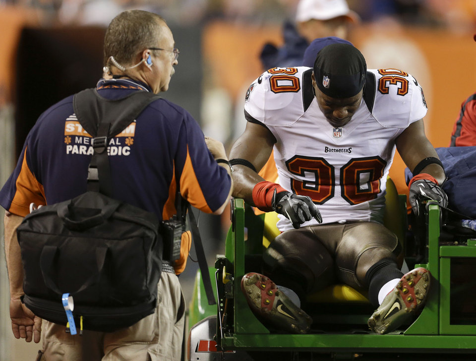 Photo - Tampa Bay Buccaneers cornerback LeQuan Lewis (30) is carted off the field after sustaining an injury during a punt return in the fourth quarter of an NFL football game, Sunday, Dec. 2, 2012, in Denver. Denver won  31-23. (AP Photo/Joe Mahoney)