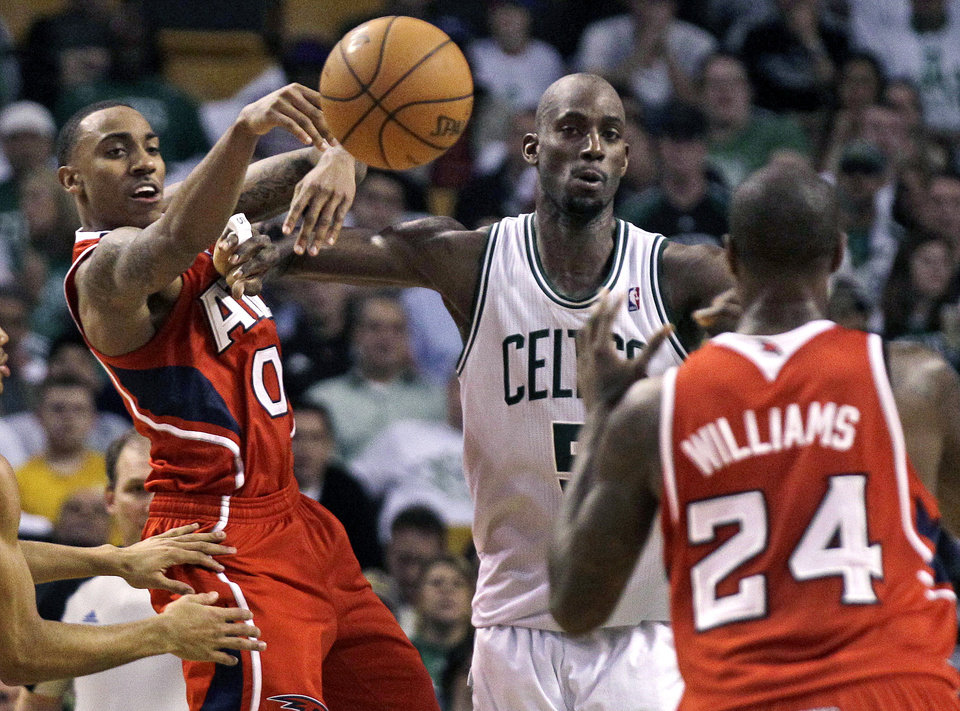 Photo -   Atlanta Hawks guard Jeff Teague (0) passes off to teammate Marvin Williams (24) against Boston Celtics' Kevin Garnett, center, during the second quarter of Game 3 of an NBA first-round playoff basketball series, Friday, May 4, 2012, in Boston. (AP Photo/Charles Krupa)