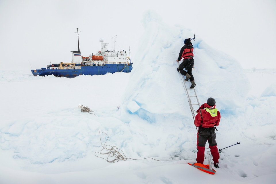 Photo - In this Tuesday, Dec. 31, 2013 image provided by Australasian Antarctic Expedition/Footloose Fotography, Ben Maddison and Ben Fisk from the Russian ship MV Akademik Shokalskiy work to place a wind indicator atop an ice feature near the trapped ship 1,500 nautical miles south of Hobart, Australia. Passengers on board a research ship that has been trapped in Antarctic ice for a week are expected to be rescued by helicopter, after three icebreakers failed to reach the paralyzed vessel, officials said Tuesday.  (AP Photo/Australasian Antarctic Expedition/Footloose Fotography, Andrew Peacock) EDITORIAL USE ONLY