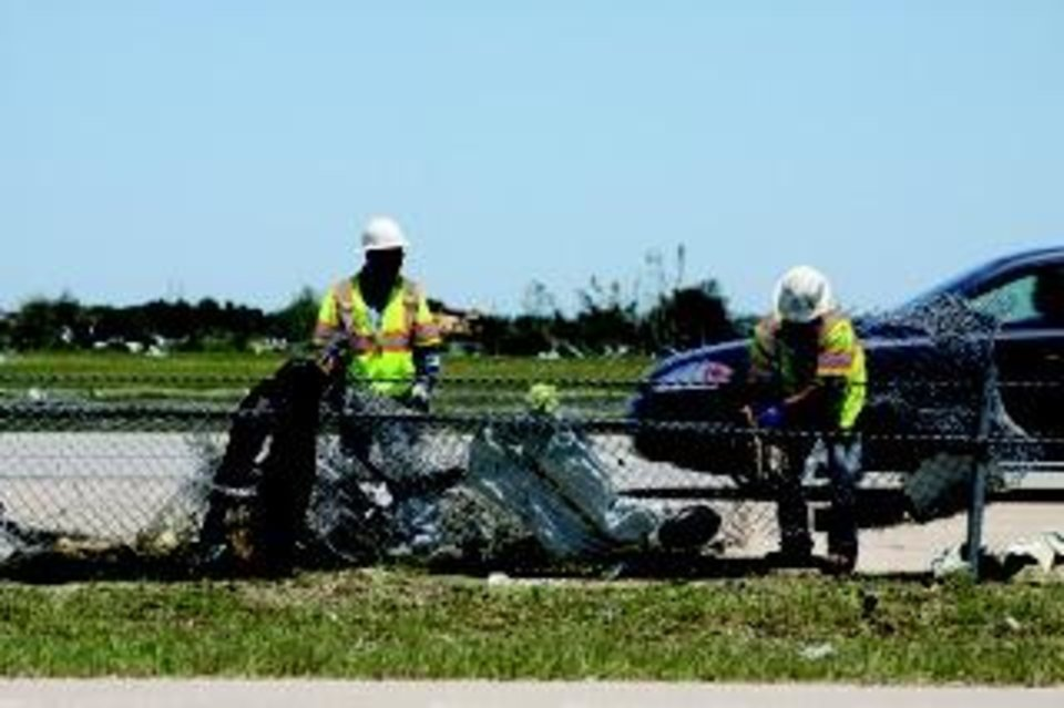 Workers clean up debris strewn along Interstate 40 Saturday. Traci Chapman