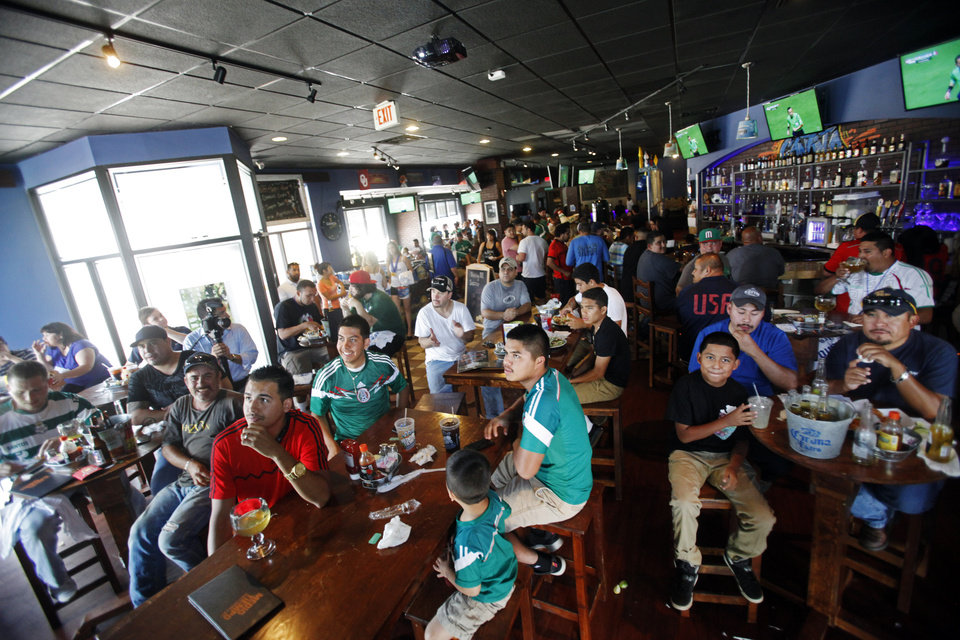 Photo -  Fans of both Mexico's and Brazil's national soccer teams crowd the tables of Medio Tiempo Sports Cantina and Grill during a World Cup watch party Tuesday for the Brazil versus Mexico game. Photo by K.T. King, The Oklahoman   KT King -