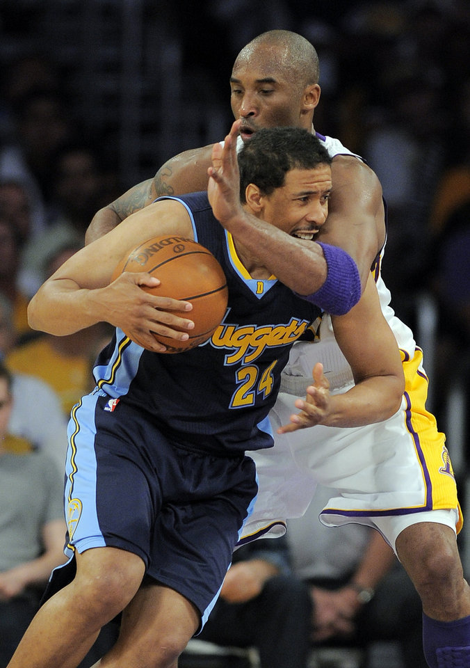 Photo -   Los Angeles Lakers shooting guard Kobe Bryant, right, fouls Denver Nuggets point guard Andre Miller as he drives to the basket during the first half of an NBA first-round playoff basketball game, Sunday, April 29, 2012, in Los Angeles. (AP Photo/Mark J. Terrill)