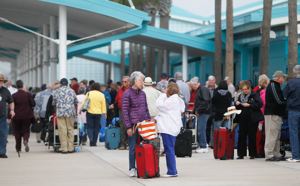 Photo - Passengers wait for their mode of transportation after getting off the Caribbean Princess cruise ship, Friday, Jan. 31, 2014, in La Porte, Texas. The ship returned to port early on Friday due to a dense fog advisory and not because people were vomiting and had diarrhea, a Princess Cruises spokeswoman said Friday. But passengers said the crew announced on the second day of the cruise that people were sick, apparently with highly contagious norovirus, and that extra precautions were being taken to ensure it didn't spread.  (AP Photo/Houston Chronicle, Cody Duty)